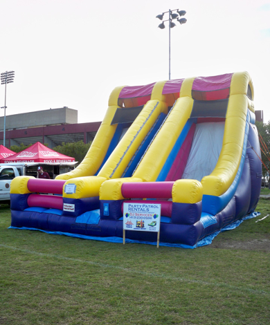 "The Dual Lane Dry Slide offered by Party Patrol Rentals is great fun at any party or event and enjoyed by kids of all ages. The stairs are located in the middle of the two dry lanes giving participants plenty of sliding fun with two riders being able to slide at the same time. It is fun to have participants race each other down the slide and riders go fast thanks to the 60-degree angle, which helps them gather speed as they slide. The slide platform is 11' 4"" with the overall area needed for the slide being capable of fitting the length of the slide being 30 feet, the width is 30 feet and the height of the slide is 18 feet.